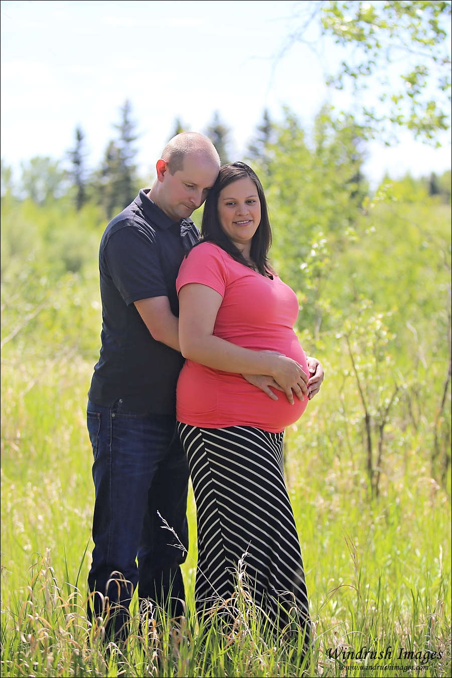 Pregnant couple in North Glenmore Park in Calgary posing in tall grass on a sunny day