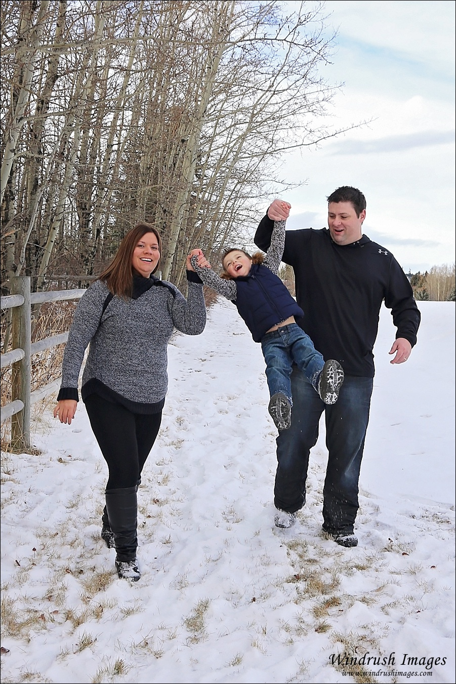 Winter family photography in Calgary of Mom and Dad swinging child in the snow while walking by a rustic wooden fence