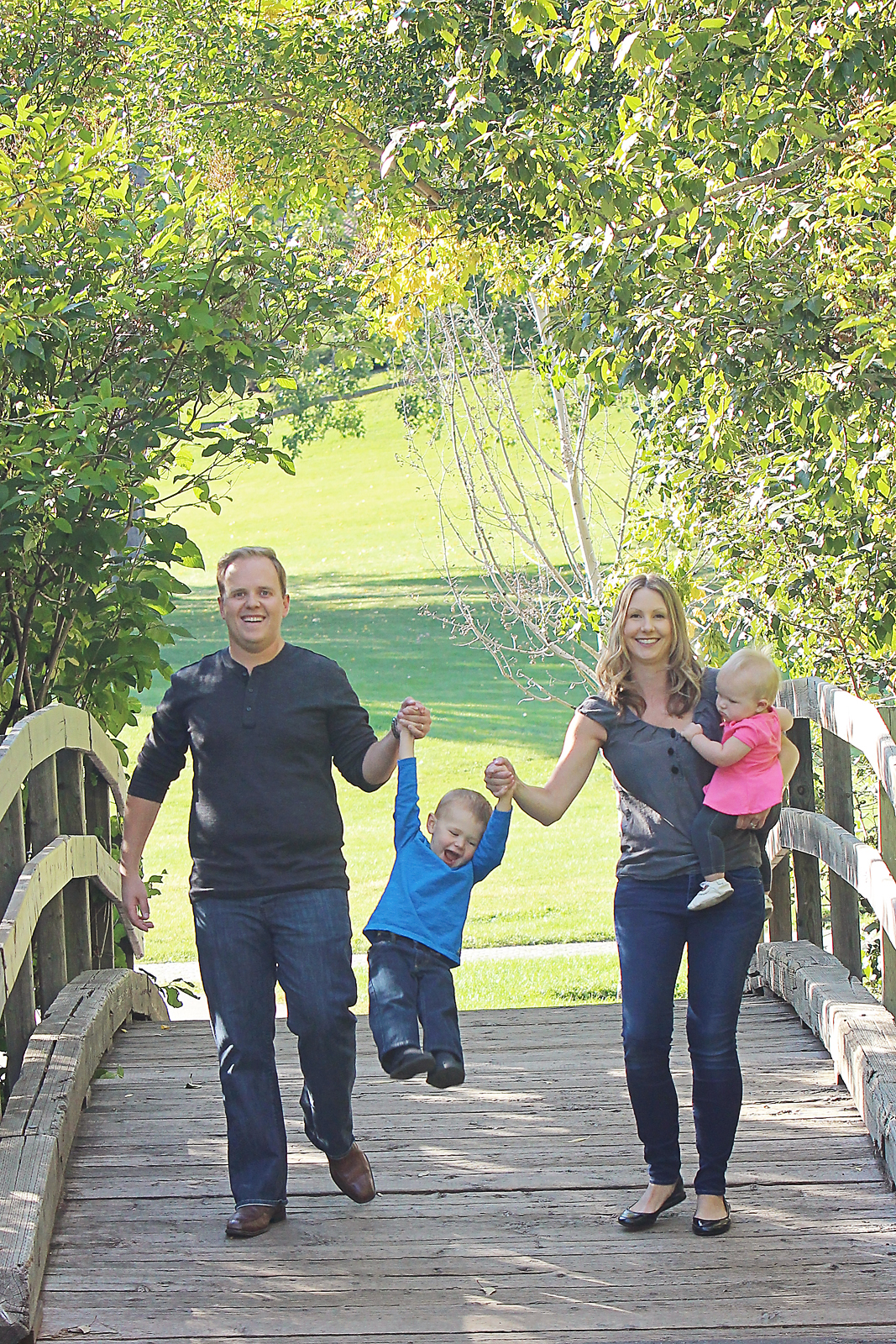 Family photo shoot in Confederation Park in Calgary with family walking over wooden bridge swinging little boy