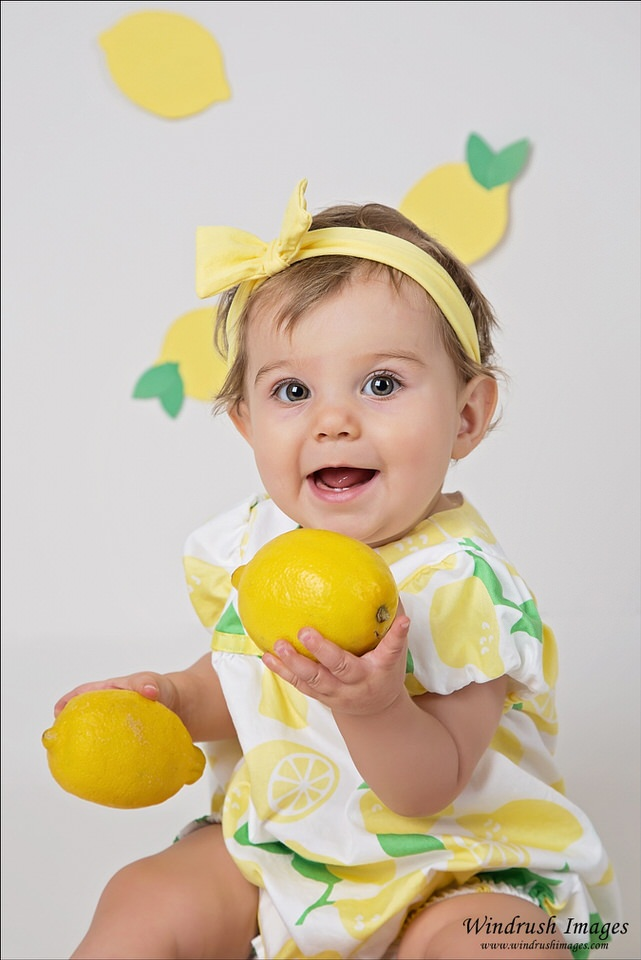 adorable-one-year-old-girl-holding-lemons-at-the-beginning-of-a-lemon-themed-cake-smash-photography-session-in-north-west-Calgary