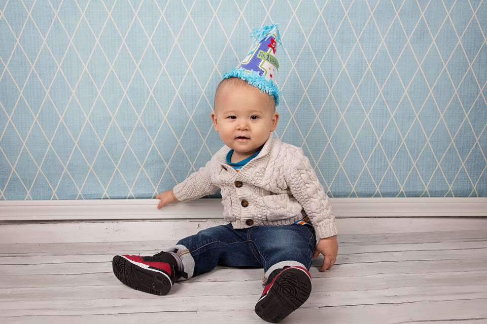 Adorable-little-boy-wearing-birthday-hat-at-milestone-session-at-Calgary-photography-studio
