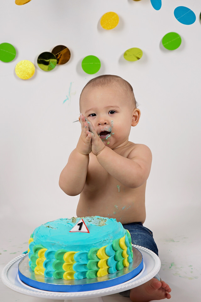 Baby-boy-at-construction-themed-Calgary-studio-cake-smash-with-blue-and-yellow-cake-and-dot-decorations