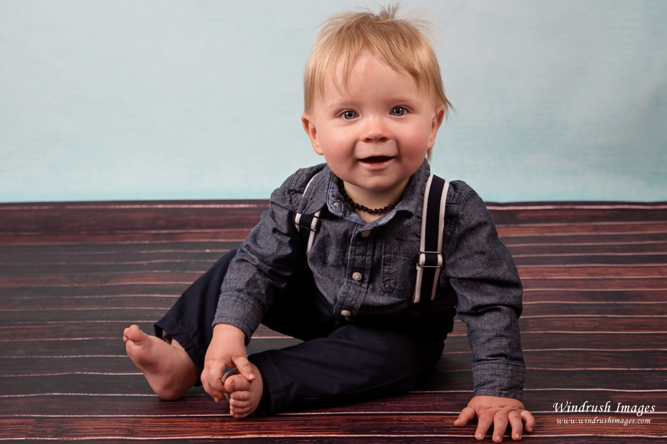 Baby-photographer-Calgary-one-year-old-boy-in-jeans-and-suspenders.jpg