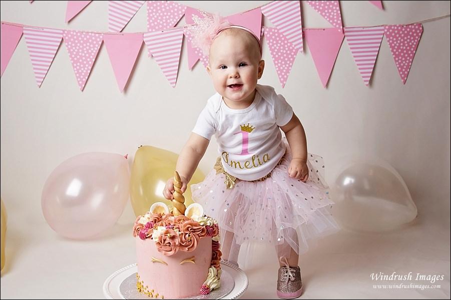 one-year-old-girl-getting-ready-to-smash-unicorn-cake-Calgary-cake-smash-photographer