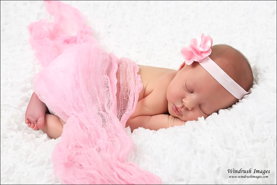 Calgary Newborn Photography baby girl sleeping with pink blanket photographed in Calgary photo studio.jpg
