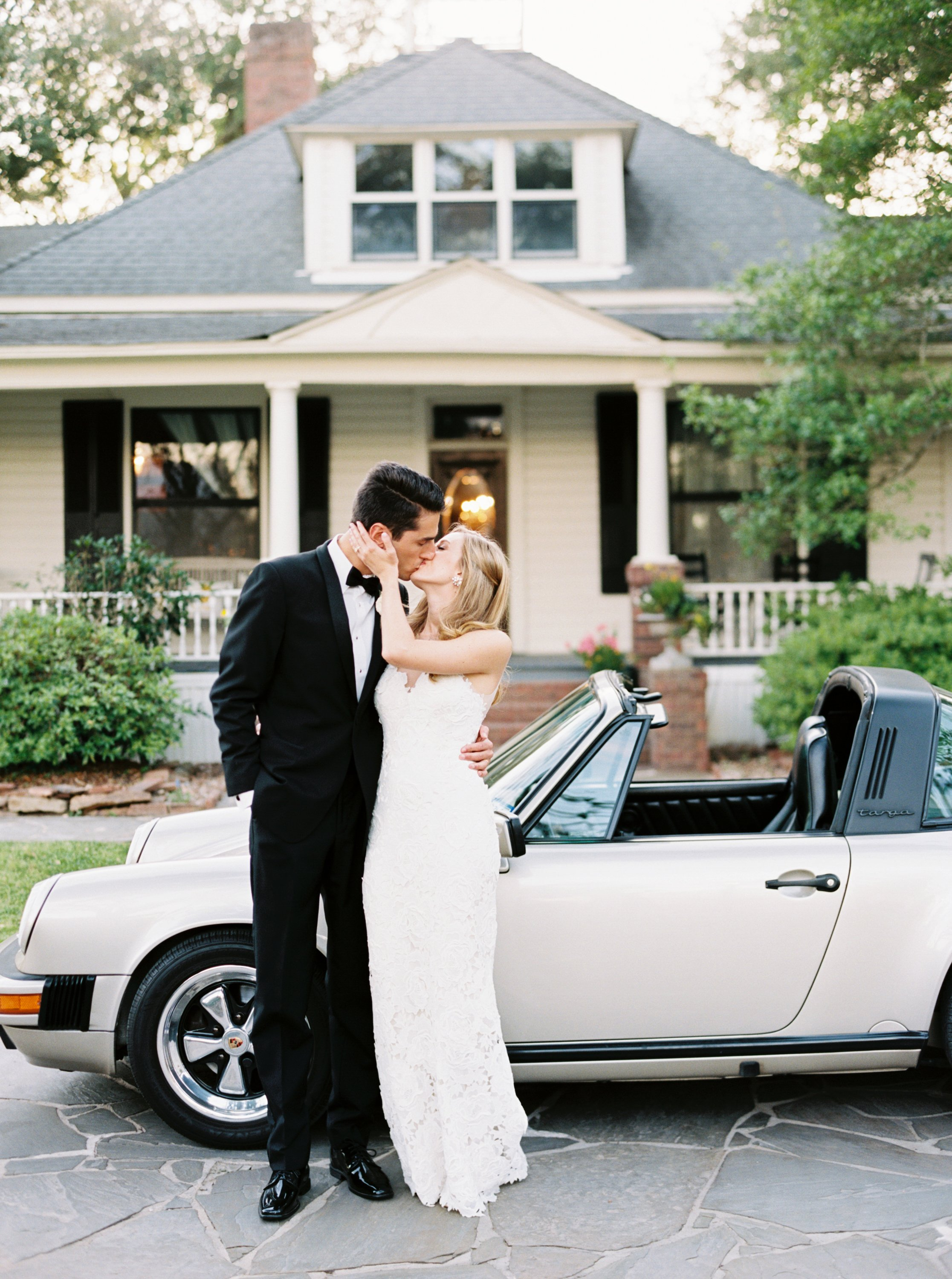 Bride and Groom kiss in front of classic getaway car  by Top Texas Wedding Photographer Hannah Mayson