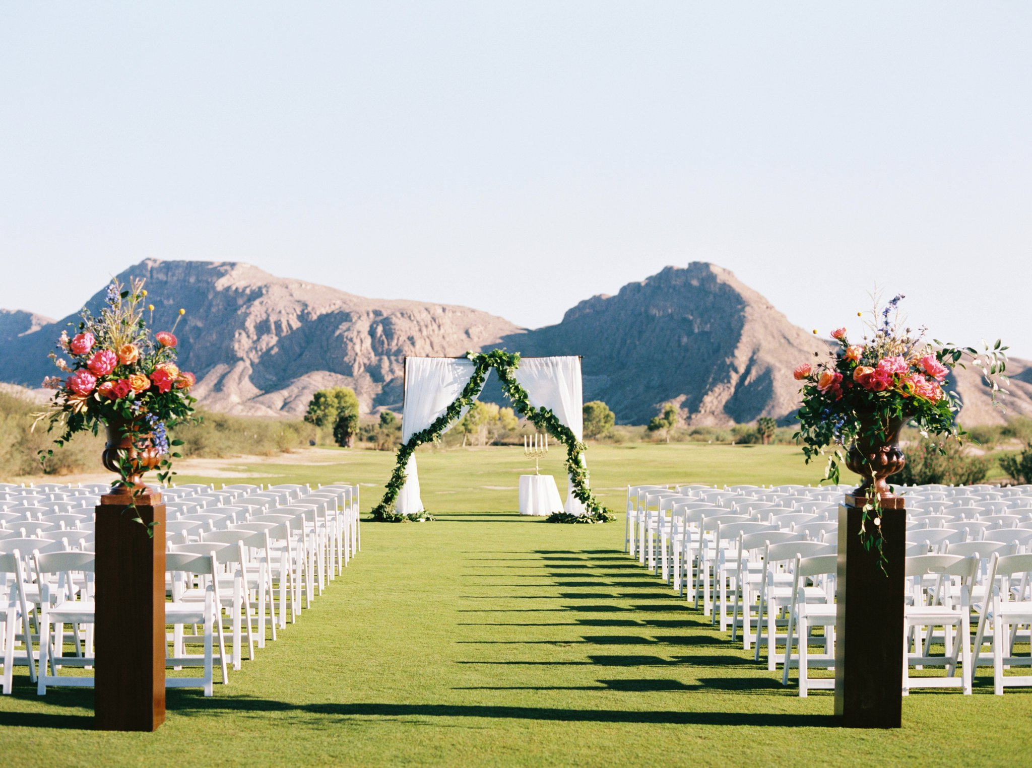 With the most stunning mountain backdrop, Lacie and Stewart used drapery and greenery to pull the audience into the ceremony. They also had the most stunning colorful bouquets leading people to the aisle. You can see more of this wedding  here . Floral Design:  Viridian Design Studio  | Venue:  Lajitas Resort