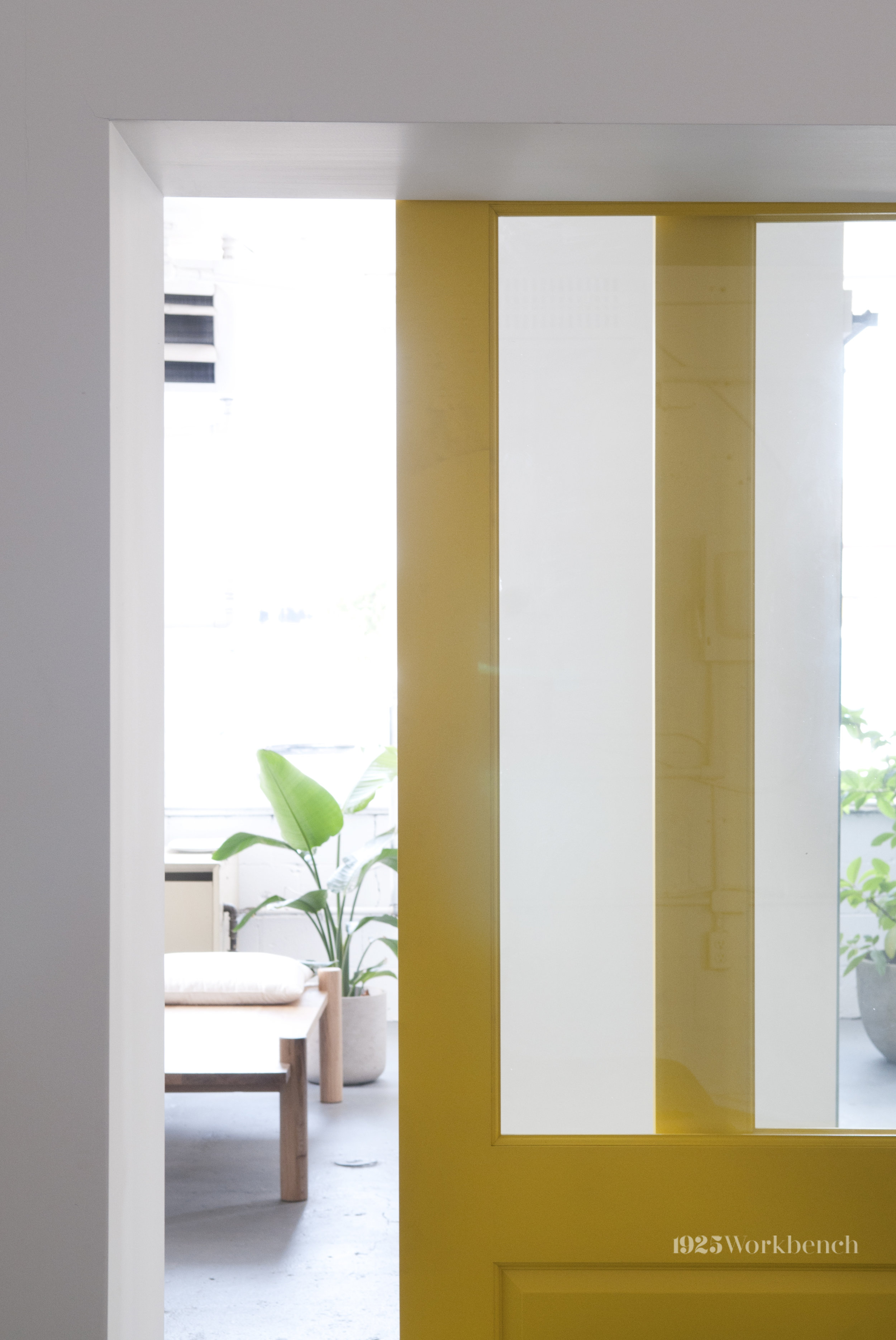 One view from the yellow doors where you see the daybed made of white oak, inspired by mid-day naps in Vietnam.