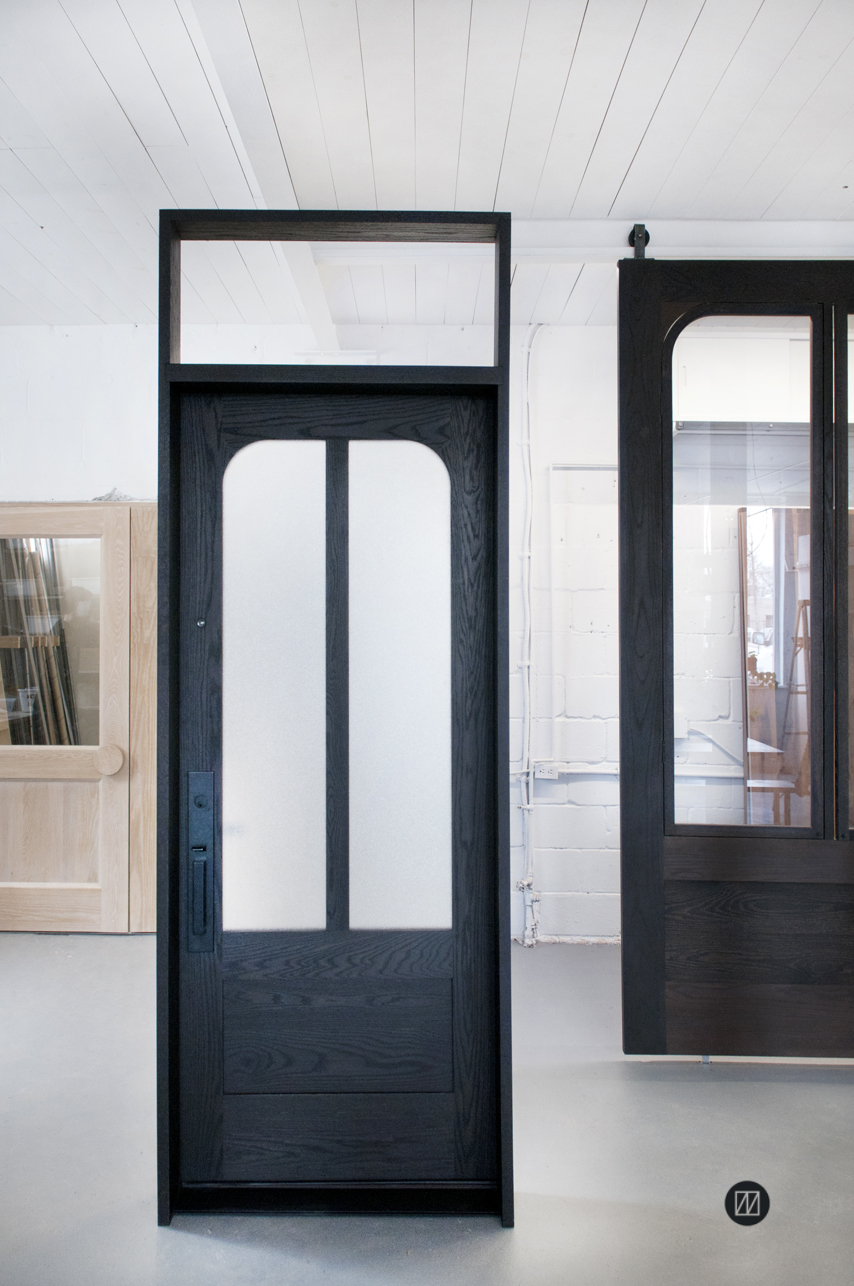 Curvy blacken oak door with transom