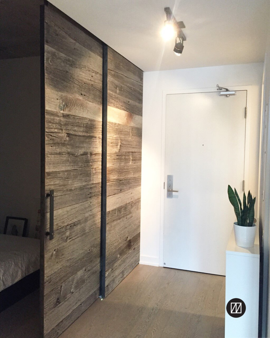 Condo bedroom: Our barn board sliding doors act as a wall to create a bedroom beyond (see on left).