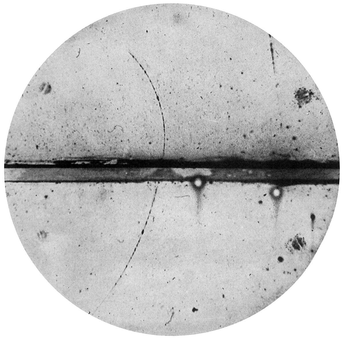 Cloud chamber photograph of the first positron identified by Carl Anderson. The existence of such a particle (the anti-electron) was mentioned in passing by Dirac in his 1931 paper on quantization of electric charge.