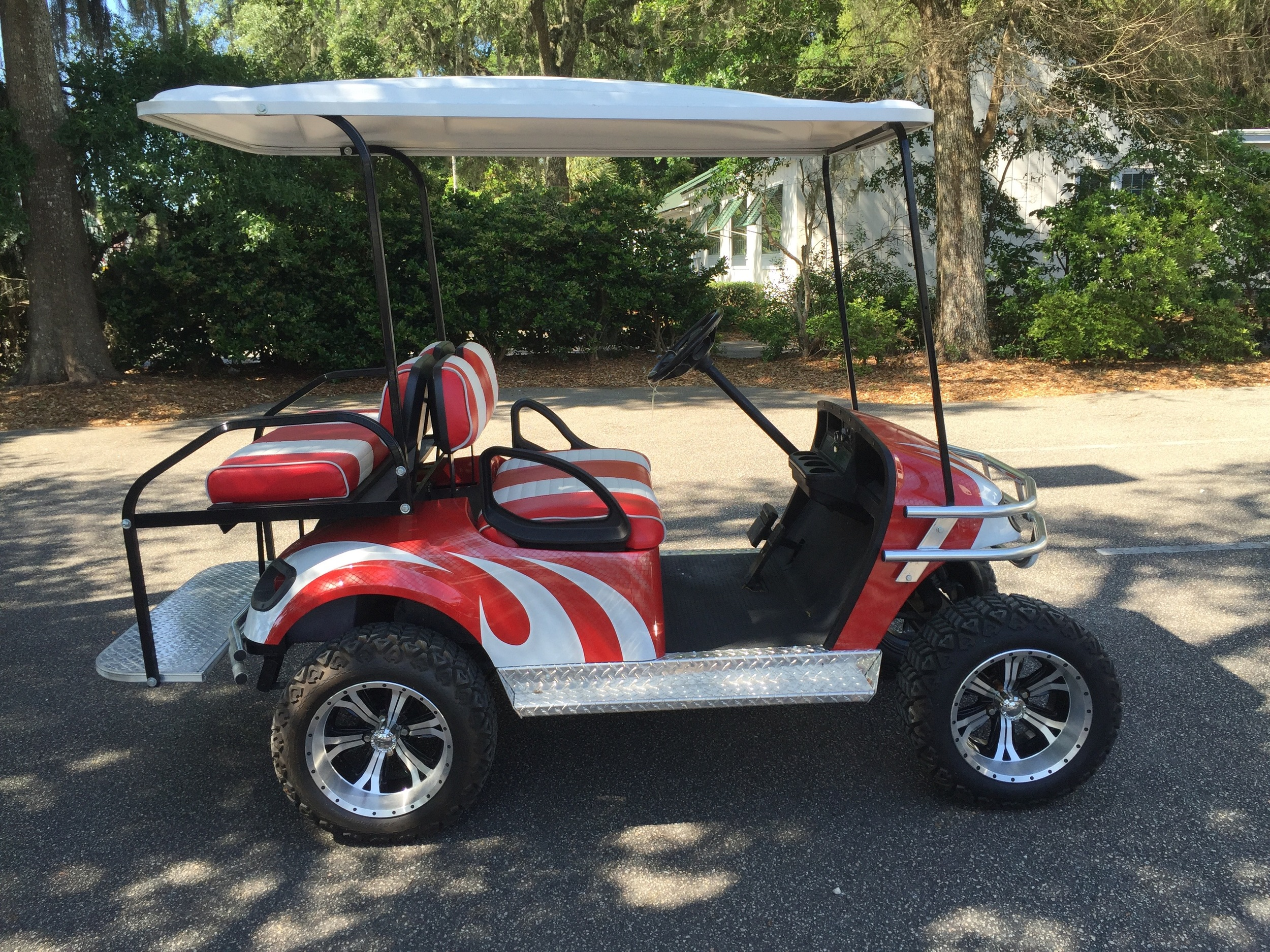 Red Swirl EZGO Lifted Cart  Red/white seats, white extended top, new batteries, high speed code, LED lights, Backlash (23x10x14) tires, chrome brush guard, running board, and rear guard