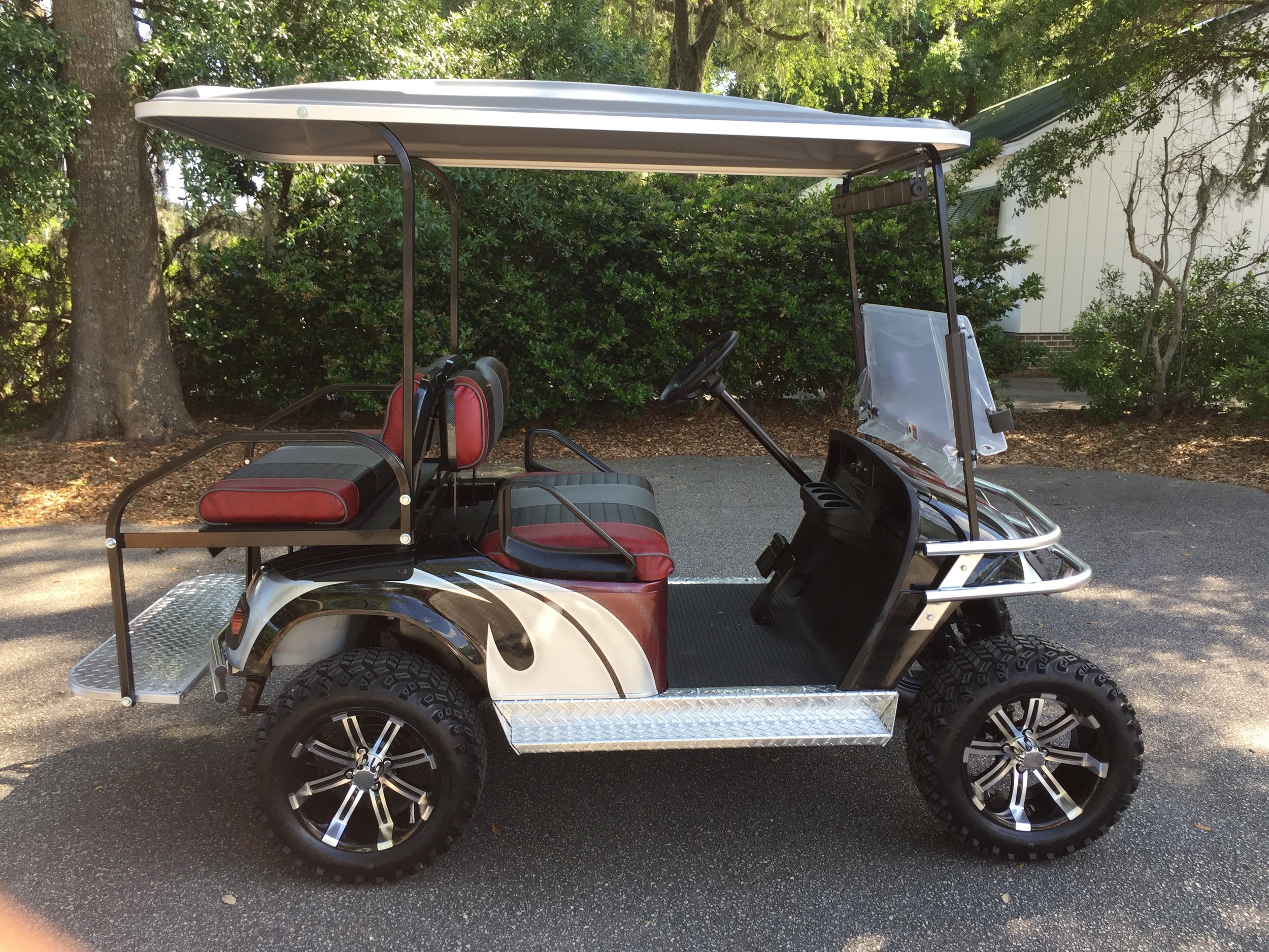 Burgundy Swirl EZGO Lifted Cart  Burgundy/black/smoke seats, black extended top, new batteries, high speed code, LED lights, Backlash (23x10x14) tires, chrome brush guard, running board, and rear guard, mirror, flip windshield, and state of charge meter