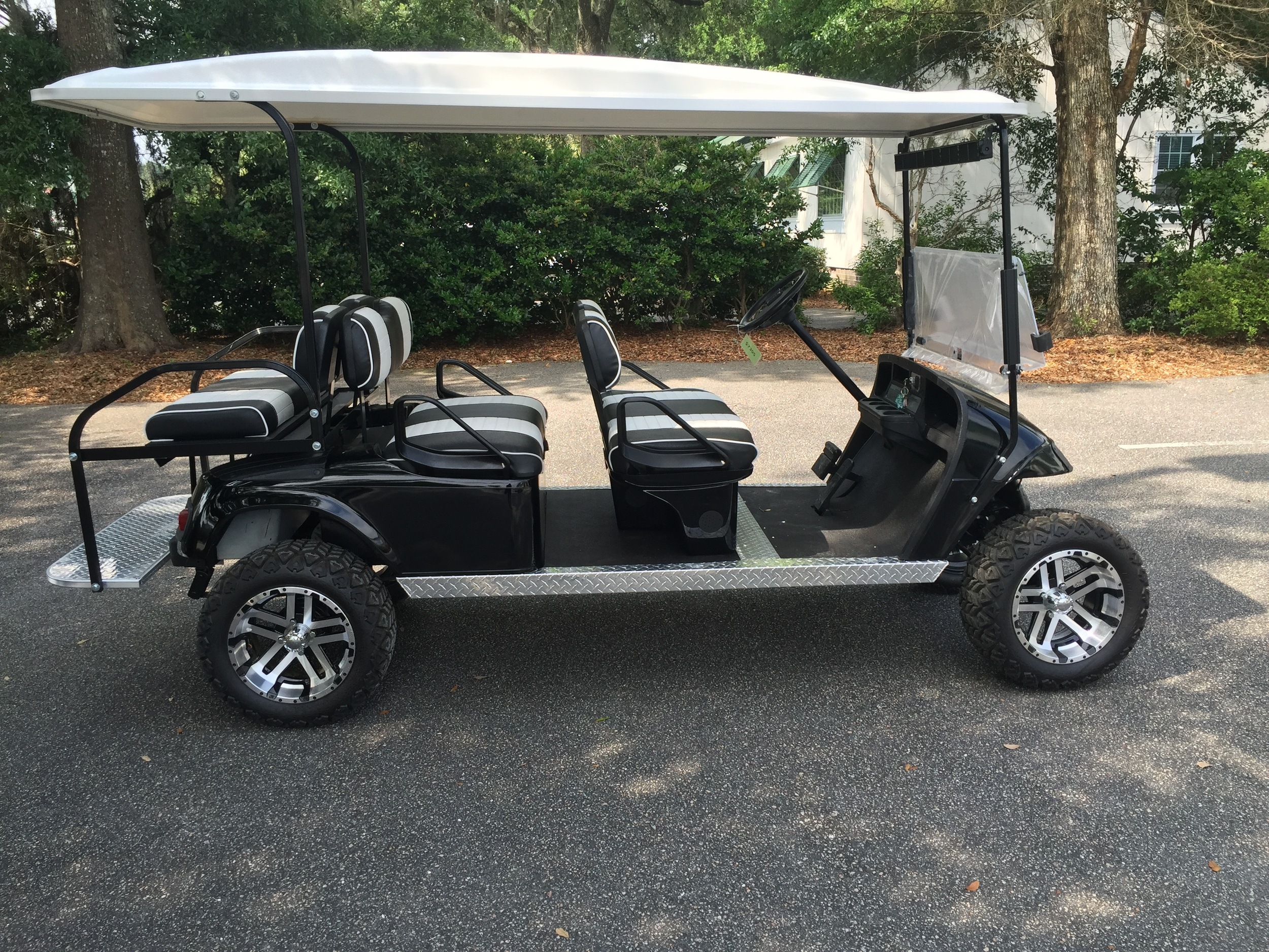 Black EZGO Lifted Trolley  Black/white seats, white top, new batteries, high speed code, LED lights, Backlash (23x10x14) tires, state of charge meter, mirror, and flip windshield
