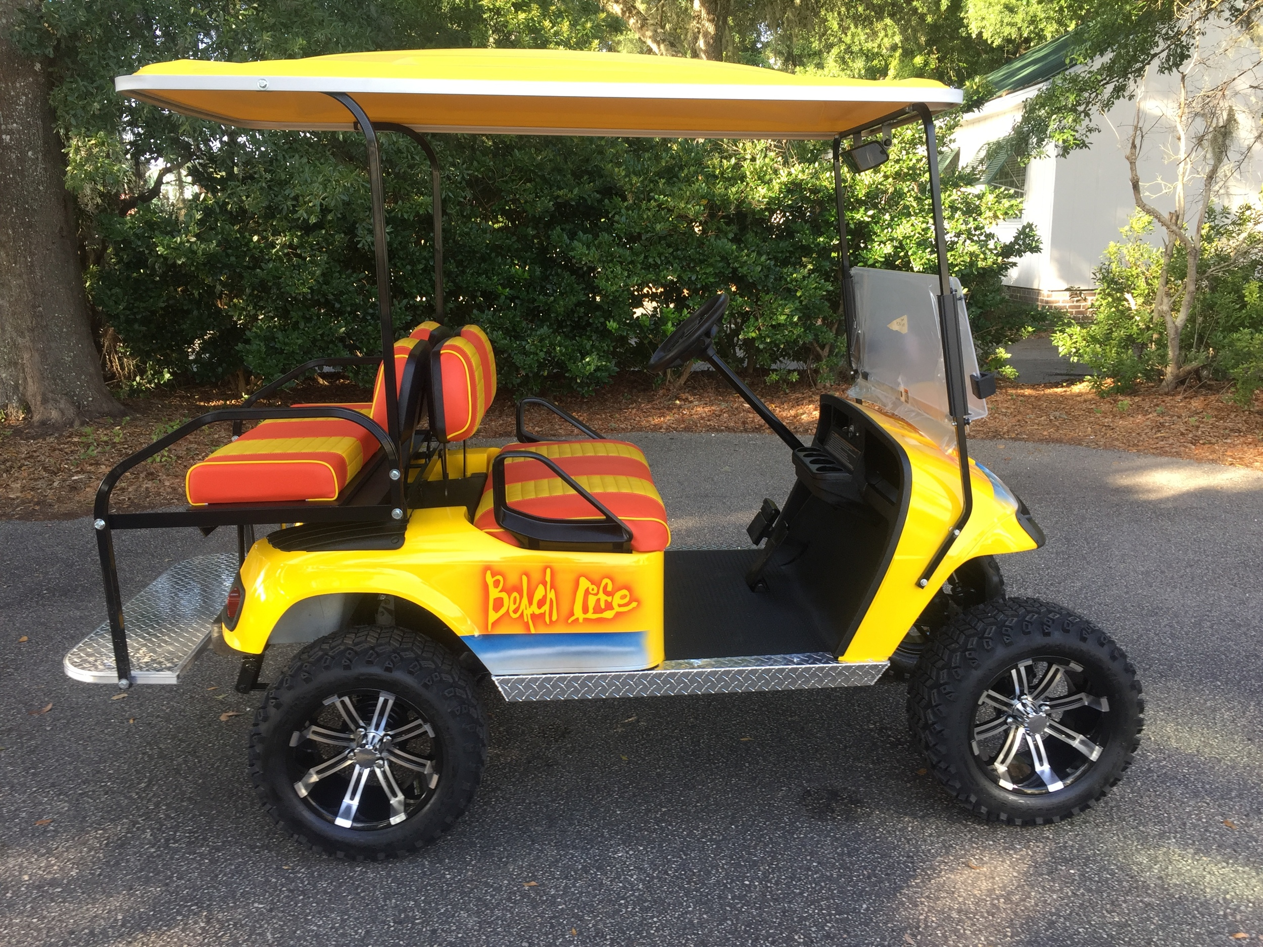 Yellow Beach Life EZGO Lifted Cart  Yellow/orange seats, yellow extended top, new 2018 (6-8vt) batteries, high speed code, LED lights, Backlash (23x10x14) tires, mirror, rear cup holders, flip windshield, and state of charge meter