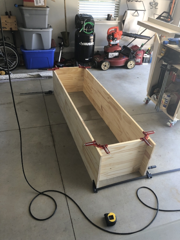 """Corner clamps and a flat surface. - With our width selected for our center shelf, we cut sections of one of our 72"""" boards to length.The top was set flush with the top of the side panels, while the bottom was raised 2in to form the legs of the kick section."""