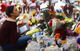 Yamileth Lopez holds a photo of her deceased friend Javier Amir Rodriguez at a makeshift memorial for victims in El Paso, Texas. (Mario Tama Getty Images)