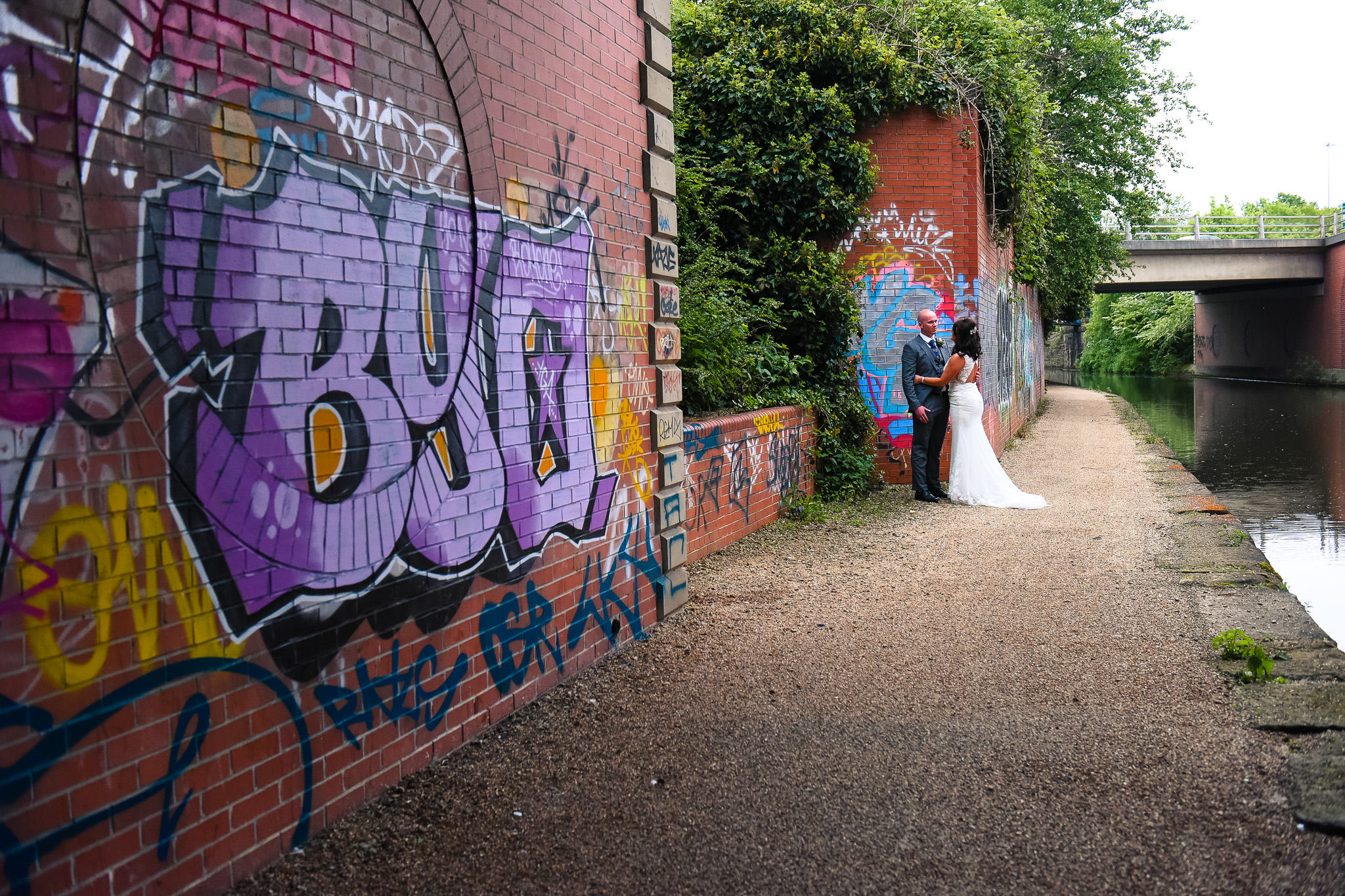 Natural portrait of bride and groom next to Manchester canal