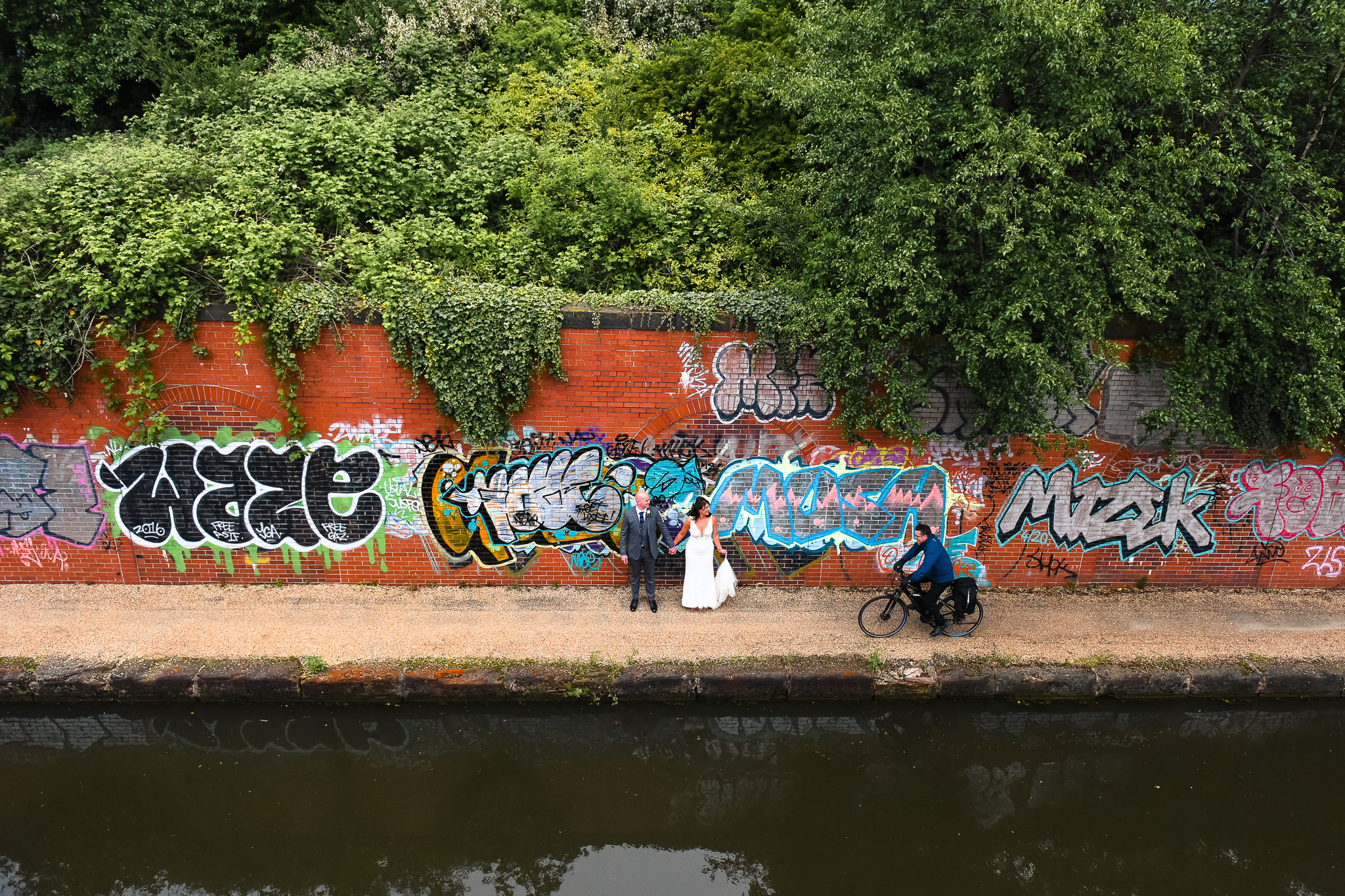 Cyclist passes bride and groom on Manchester canal