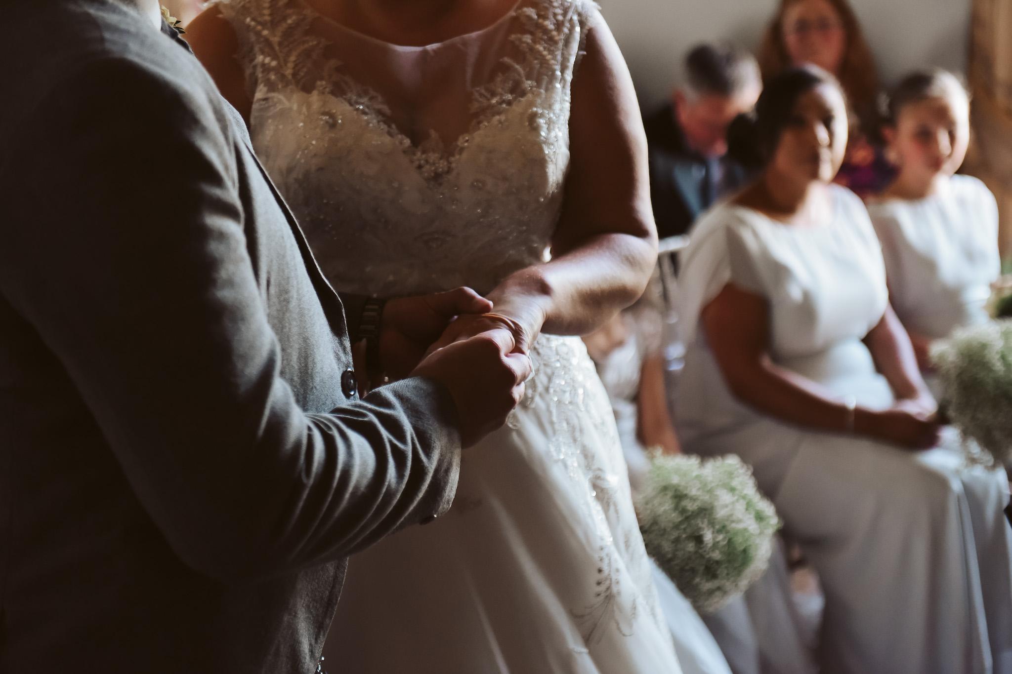 Groom placing wedding ring on bride's finger