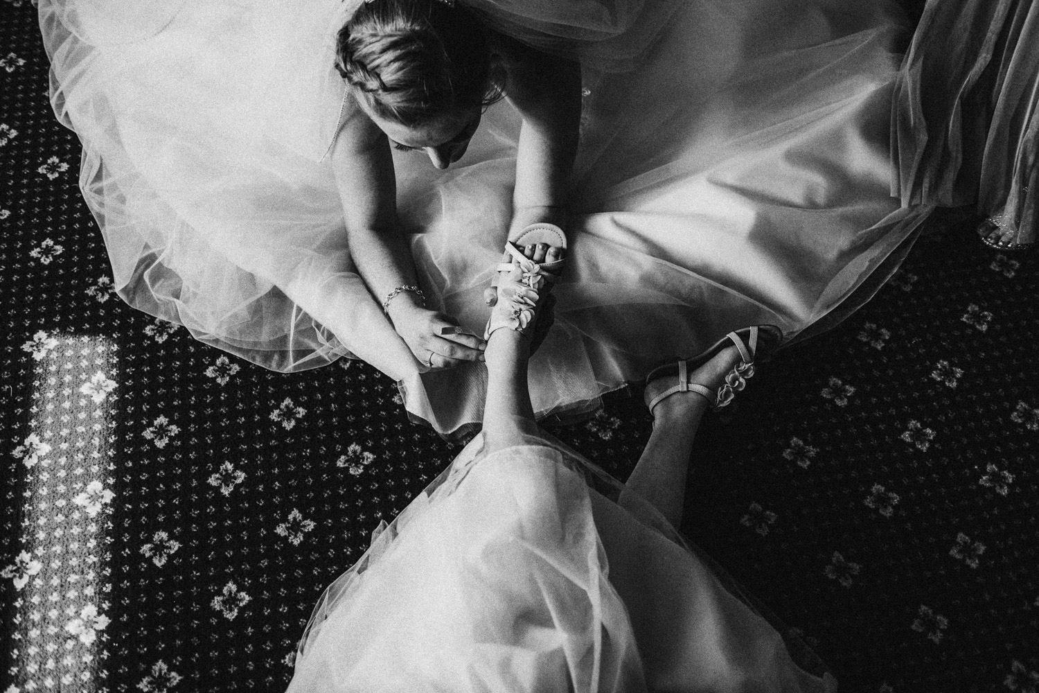 bride helping daughter with shoe