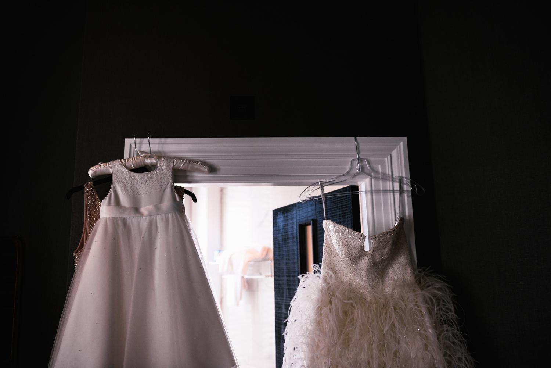 Bride's dress hanging from door frame unposed