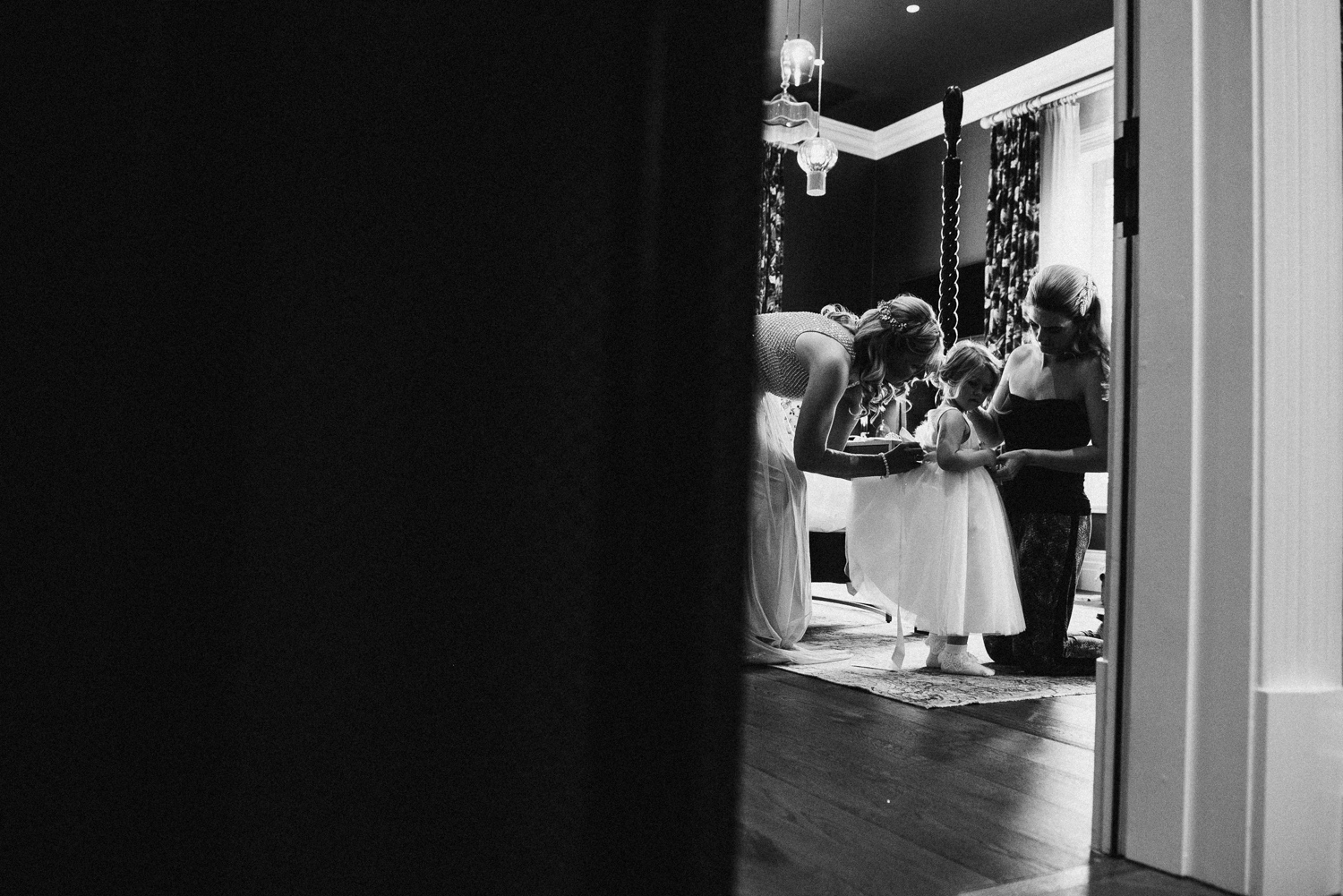 Bride helping daughter into dress