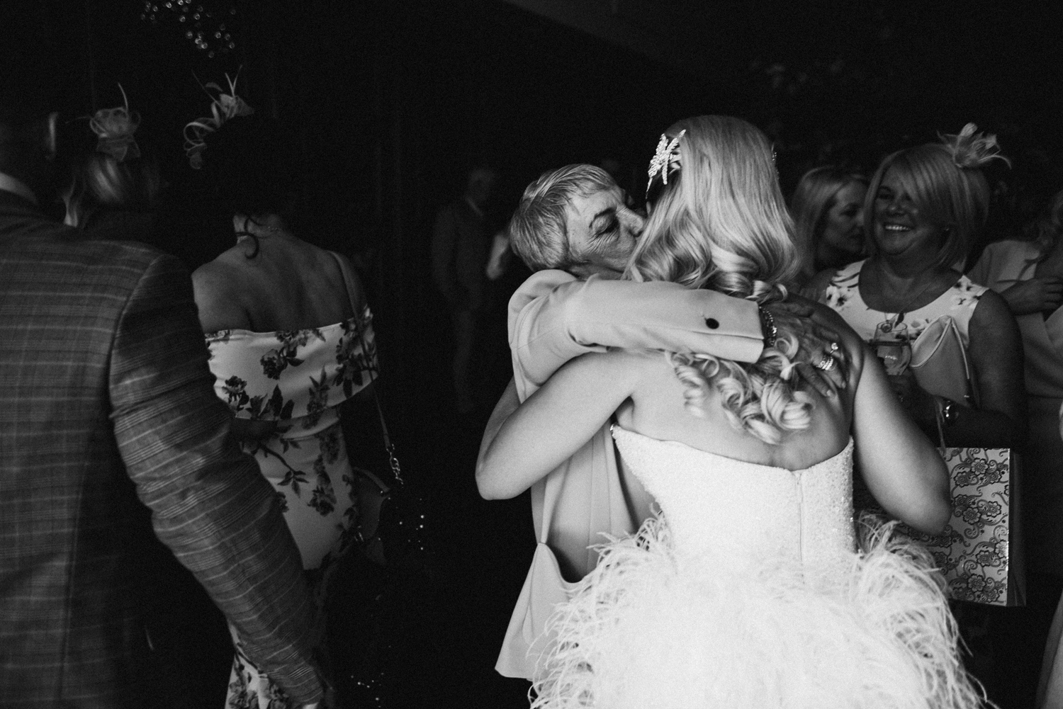 bride being hugged by guests