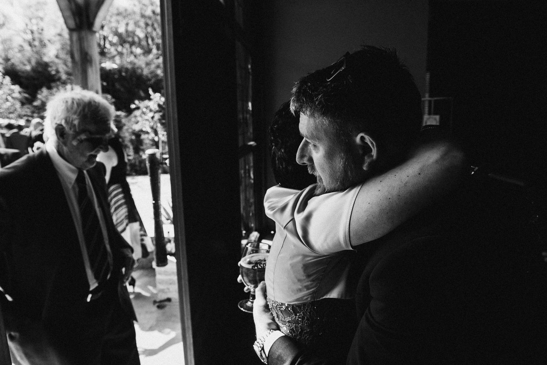 Groom hugging the humanist celebrant