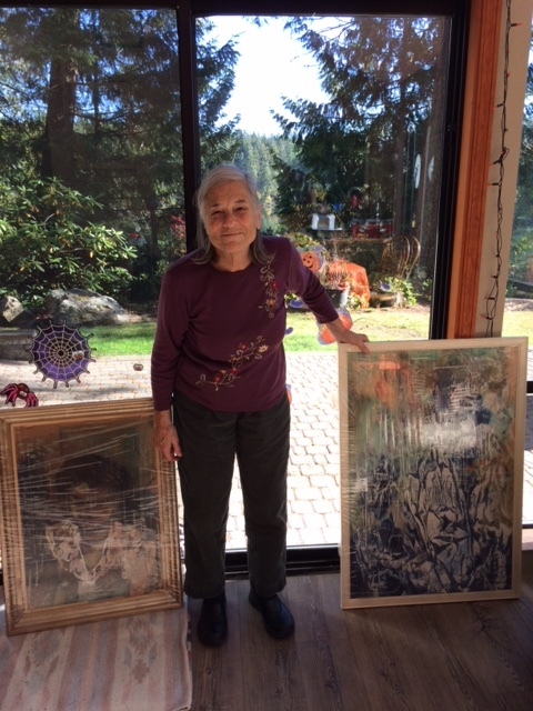 Monica Smith stands with two paintings by her father.