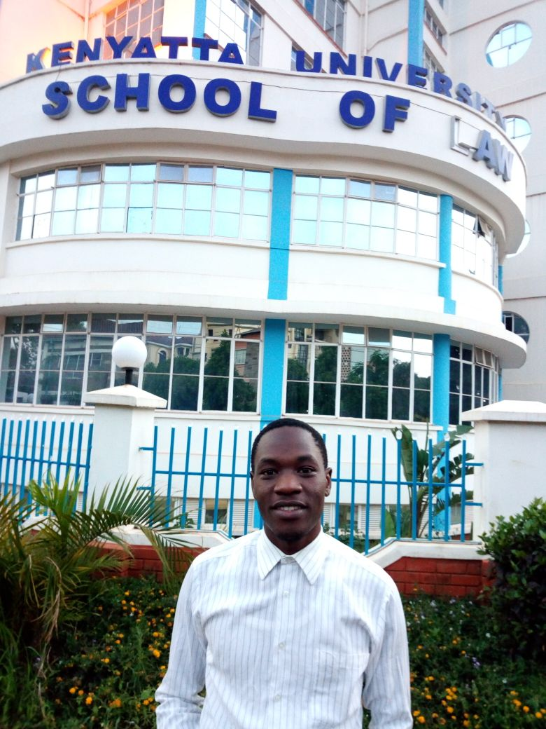 Aaron, standing outside Kenya University School of Law, where he is currently in his third year.