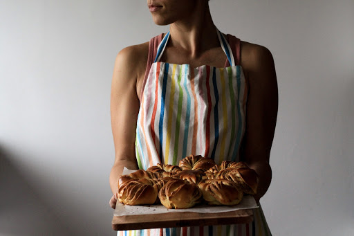 Woman holding wooden plate of cinnamon buns wearing striped apron