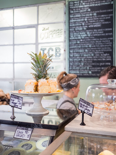 Pineapple cake and other baked goods on display in bakery with two people and menu blurred in background