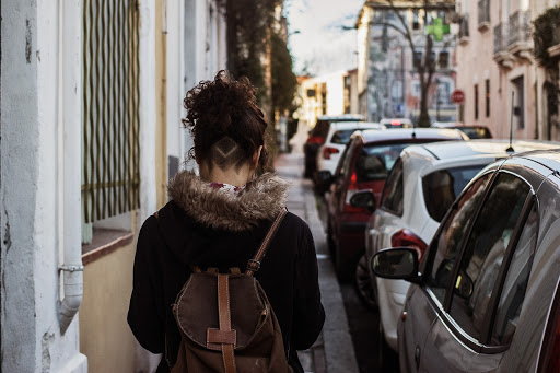 woman walking down narrow city sidewalk with shaved haircut, black coat with faux fur hood, and brown backpack