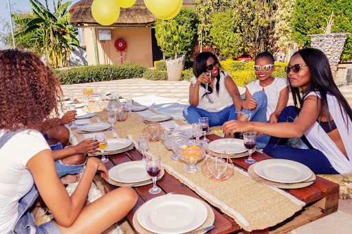 four women wearing sunglasses, jeans and white shirts drinking and eating around long table outside
