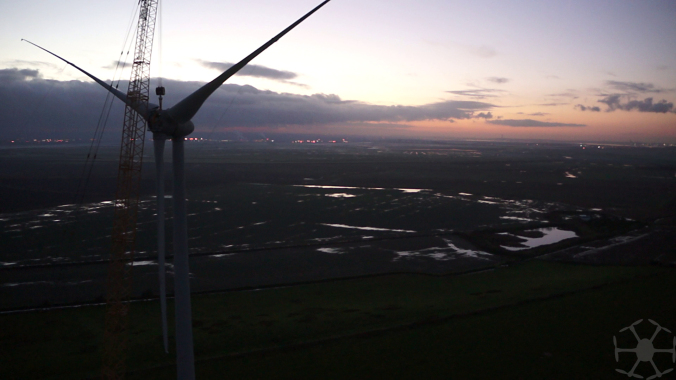 Dusk falls as the blades and hub being held in place by the crane while two engineers fix it in place from inside the nacelle
