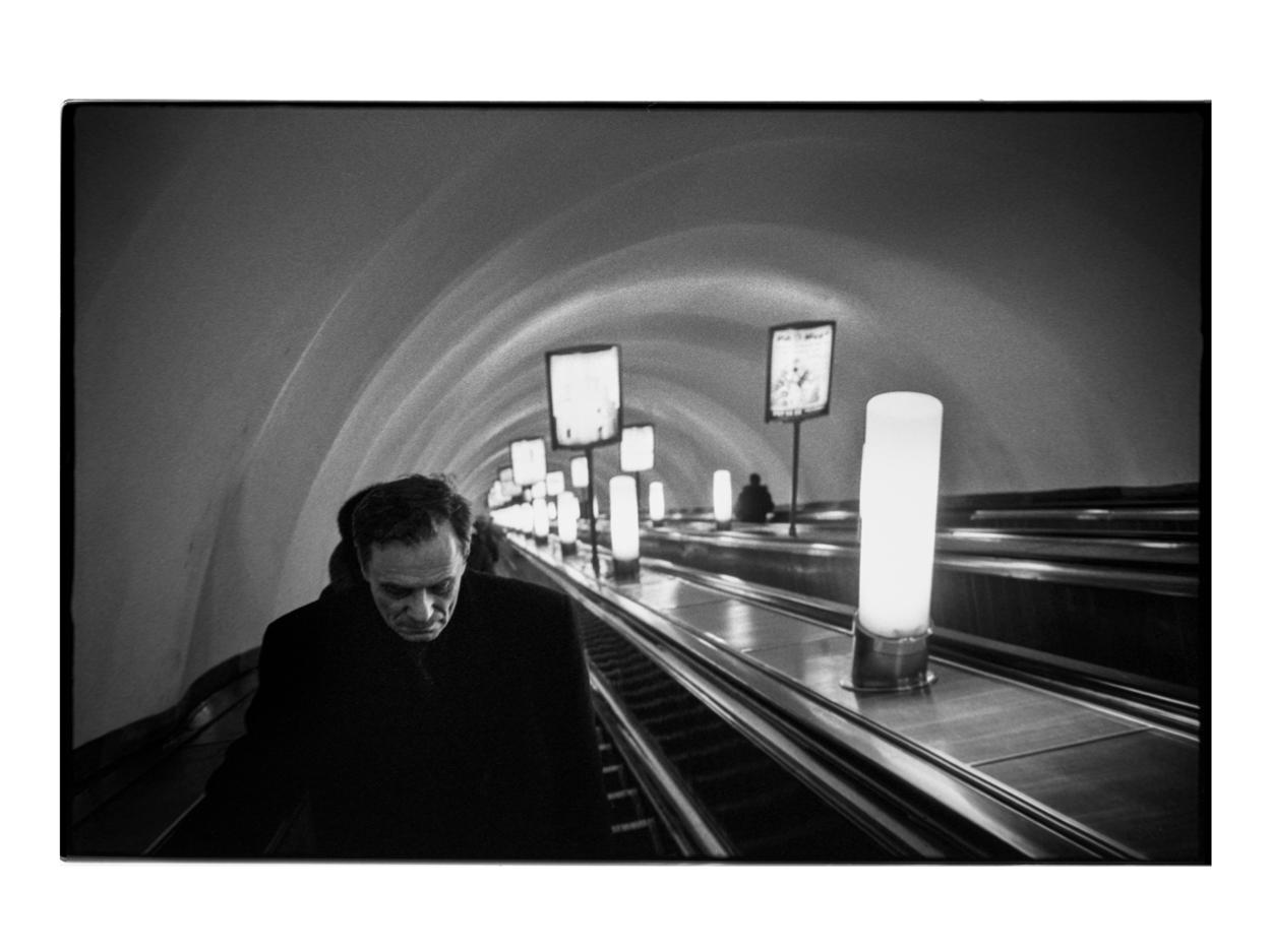A drunken man ascending the Saint Petersburg metro.