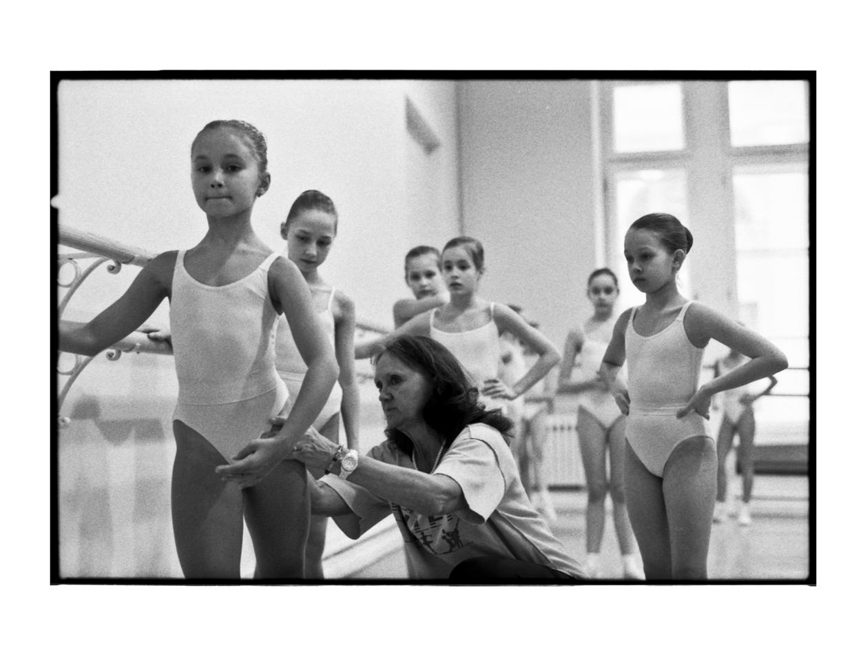 Tatiana and her classmates watch their ballet teacher explain and correct a ballet position.