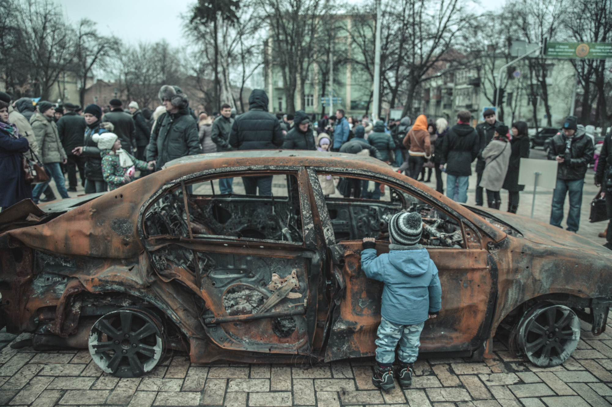 © Sam Asaert - Child looking at a burned out vehicle