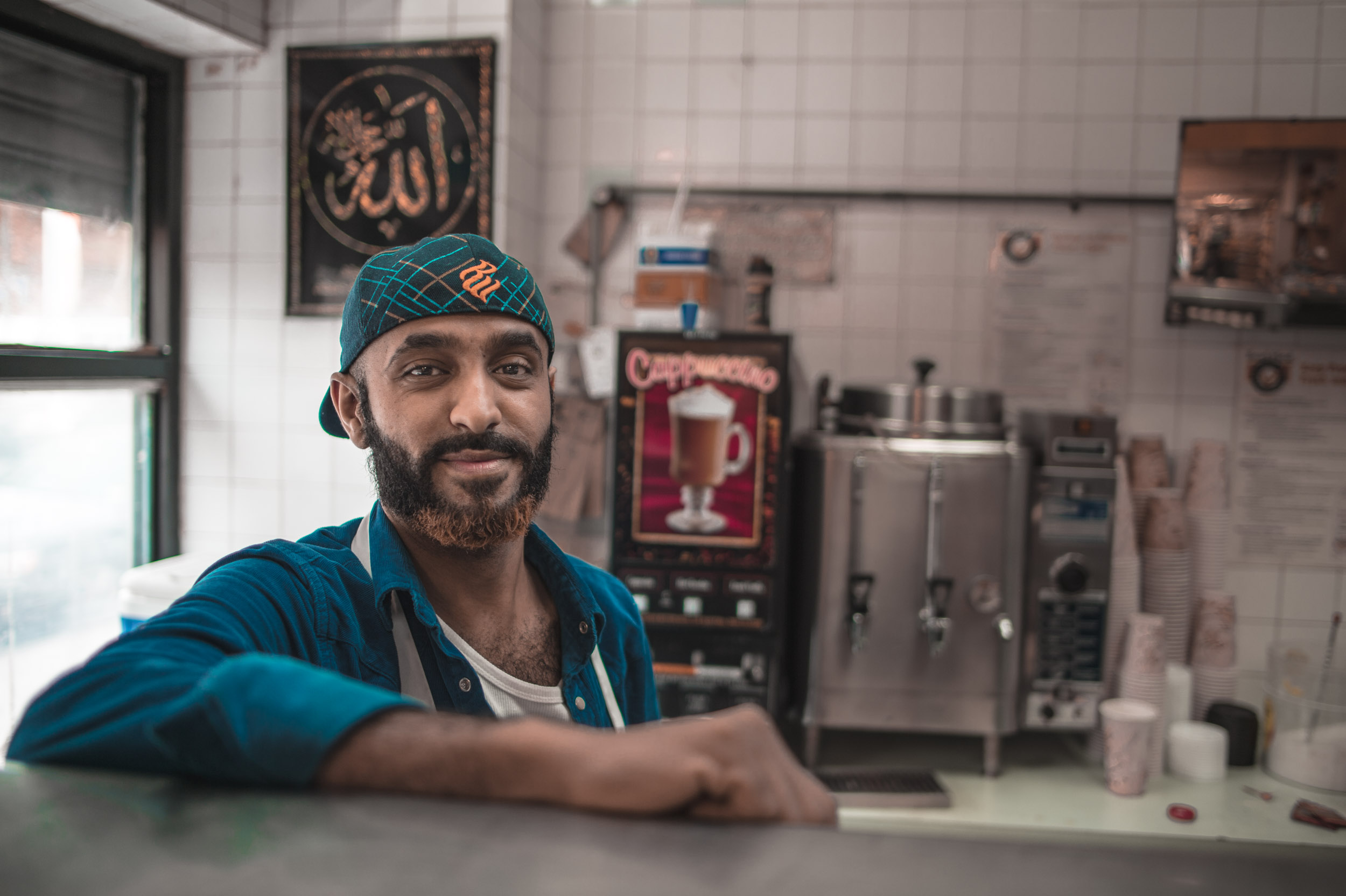 Ahmed , a Yemeni New Yorker, working the grill inside a Fort Greene bodega.