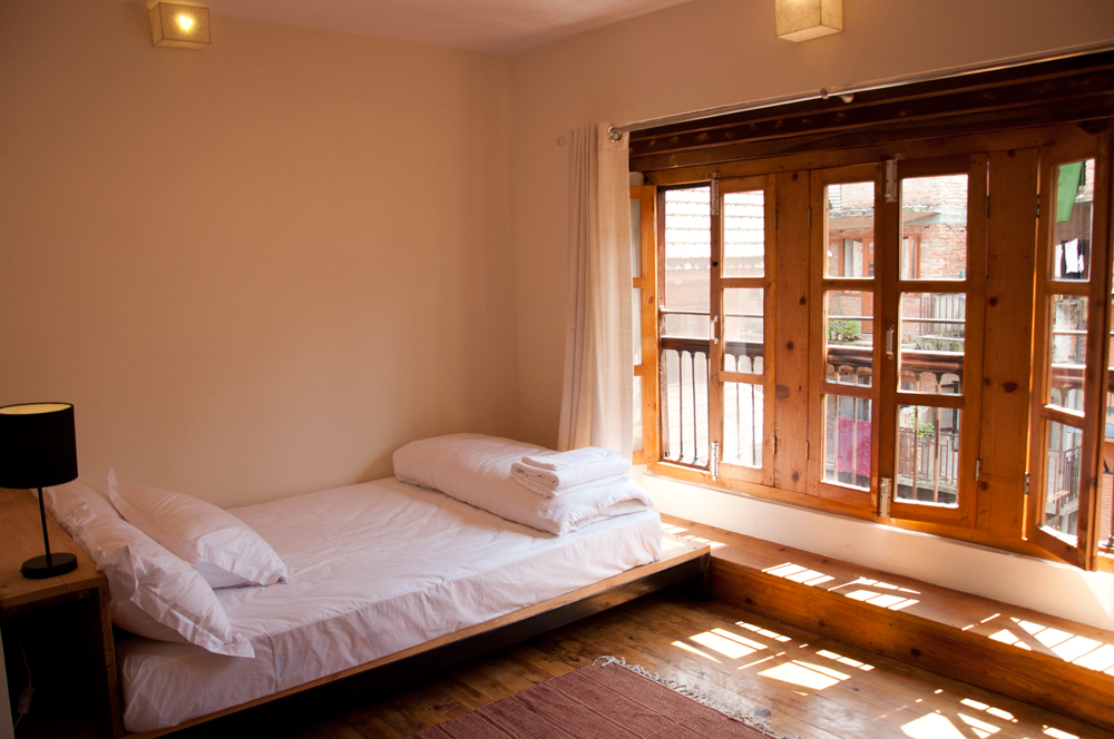 Queen bed and window to view the back part of house where there is beautiful garden.