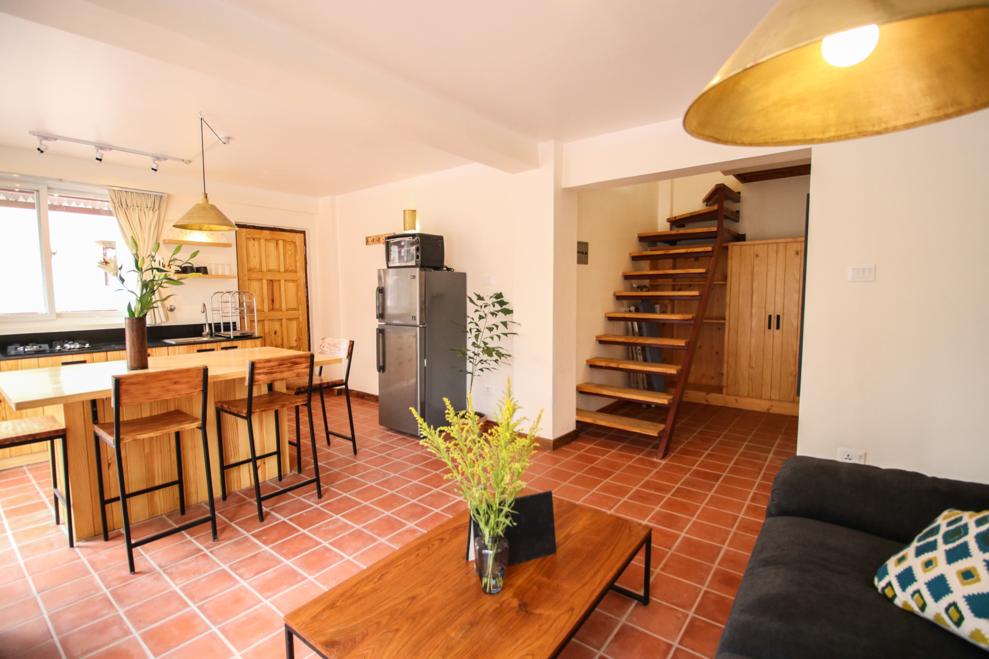 In the first floor of Roof Top Duplex there you have well equipped kitchen along with small resting space with couch.