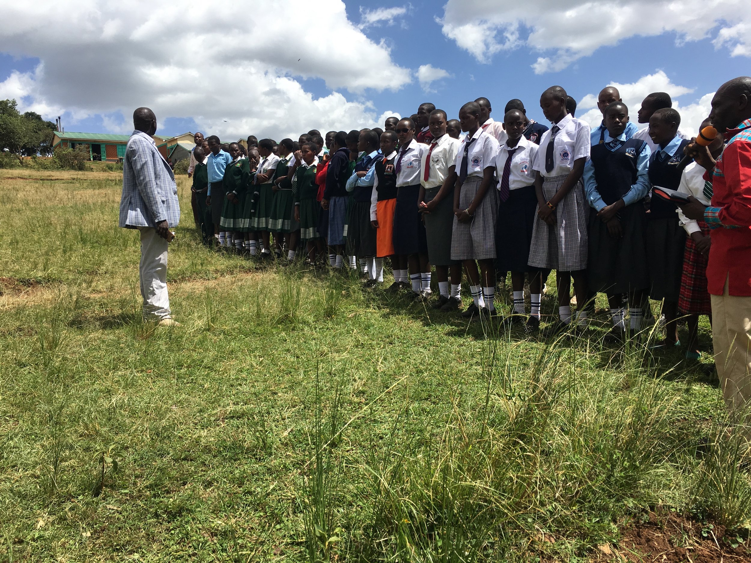 Graduates line up outside of school wearing their new uniforms.