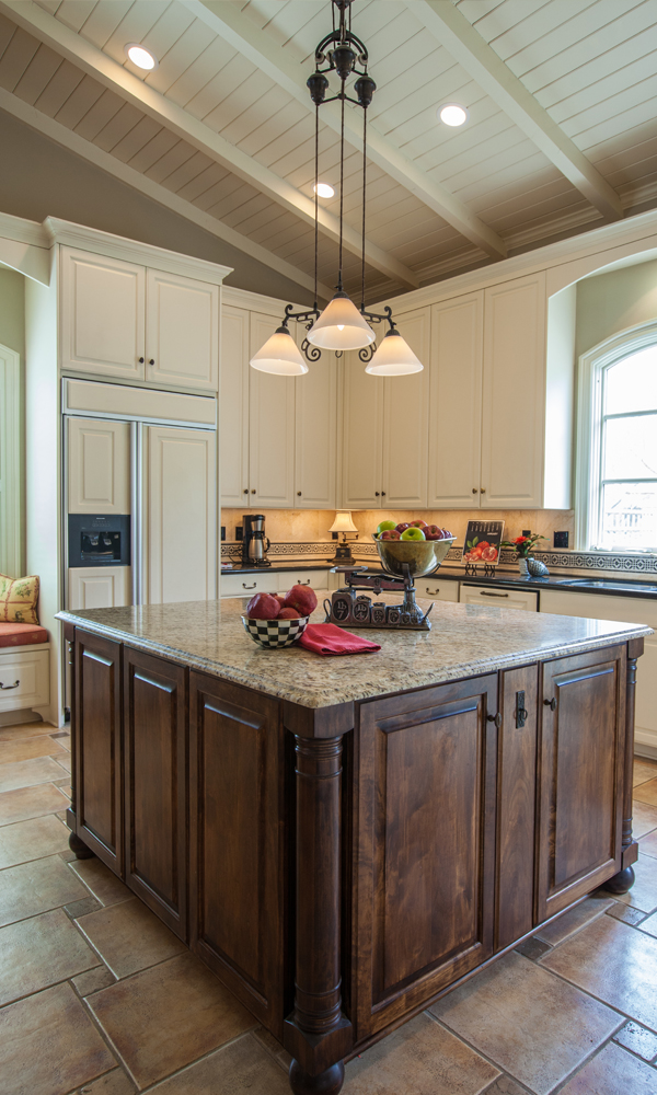 The refrigerator features front panels designed to match the adjacent cabinetry. The dishwasher, mostly obscured by the island, also features a custom panel front.