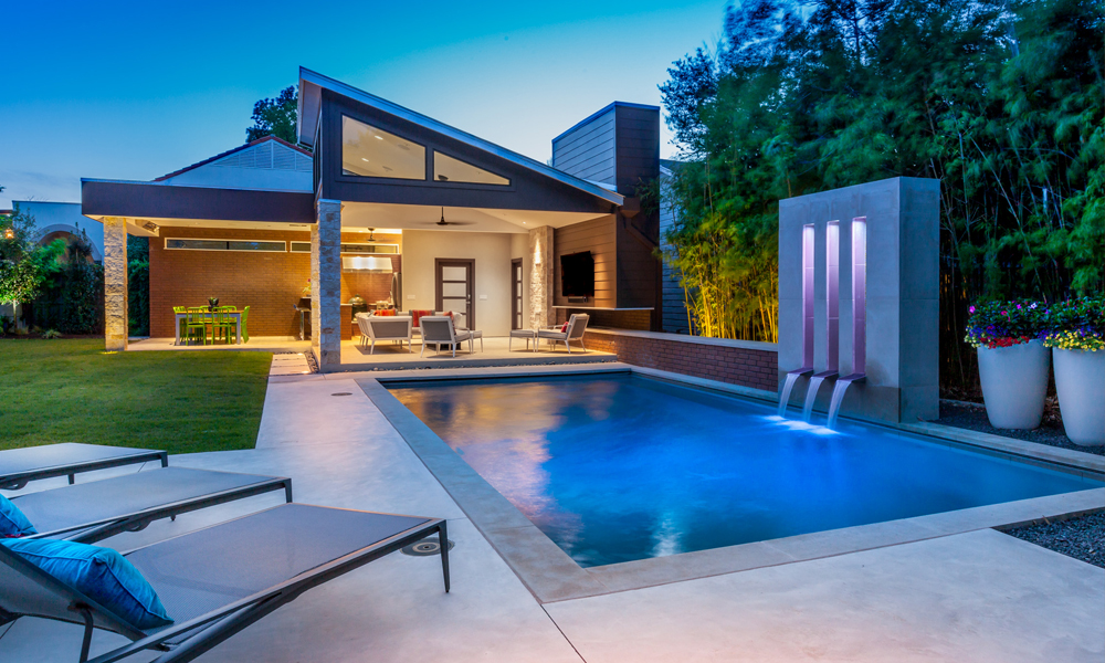 These homeowners wanted to create an entire outdoor oasis. This pool house cabana features a large outdoor kitchen, dining area, entertainment area, and enclosed pool bath. Its proximity to the pool makes it easy to use both areas without feeling much of a separation between the two key outdoor living features.