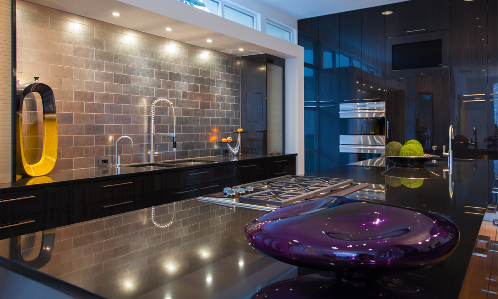 By spreading out major appliances, this kitchen can easily accommodate multiple users. The oven is located along one wall, the main sink along another, and the island houses both the range and an additional sink, all without having to sacrifice ample countertop space.