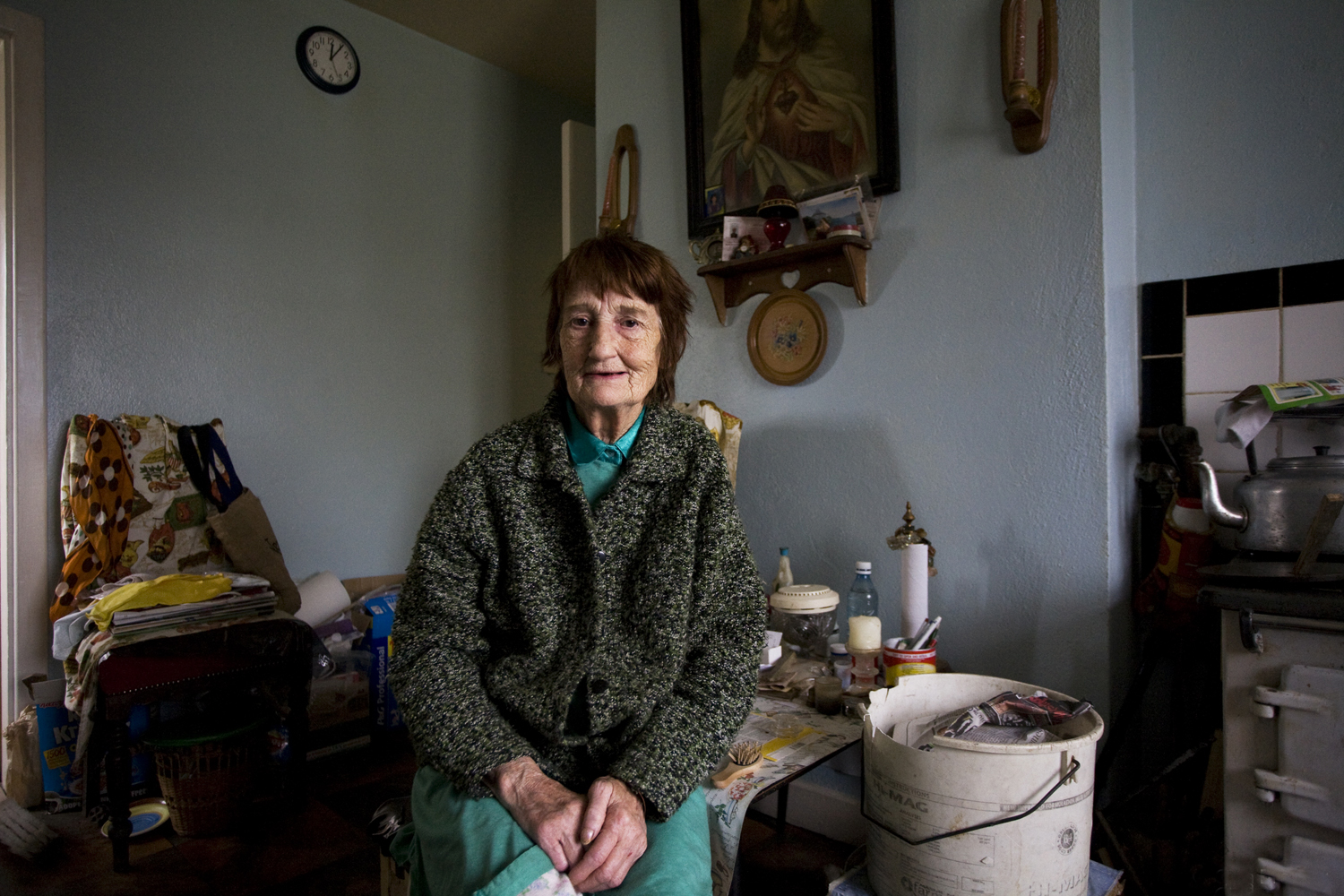 A documentary photograph of a woman sitting in her home in the west of ireland