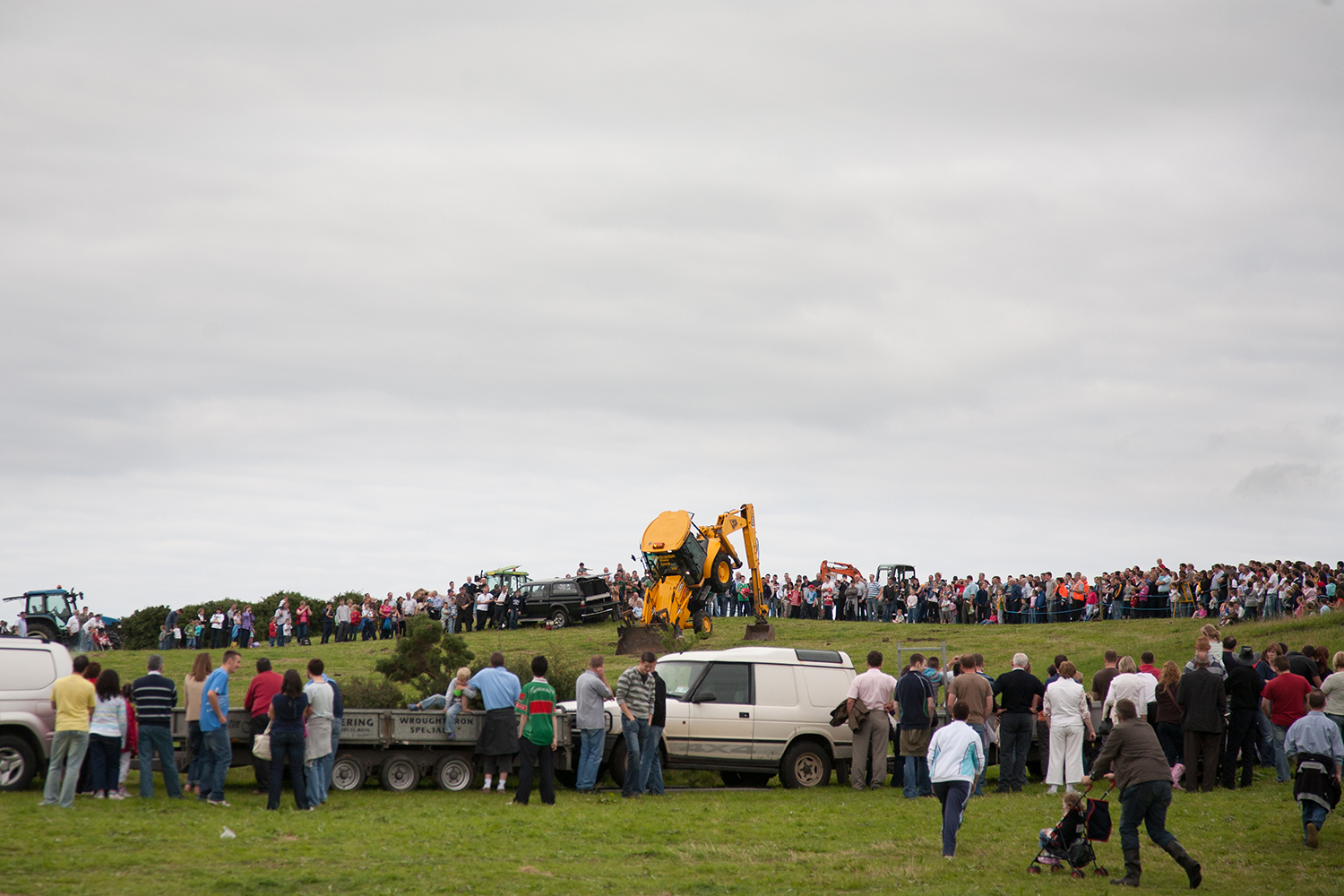 A documentary photograph of a people watching a jcb perform at an agricultural show in the west of ireland