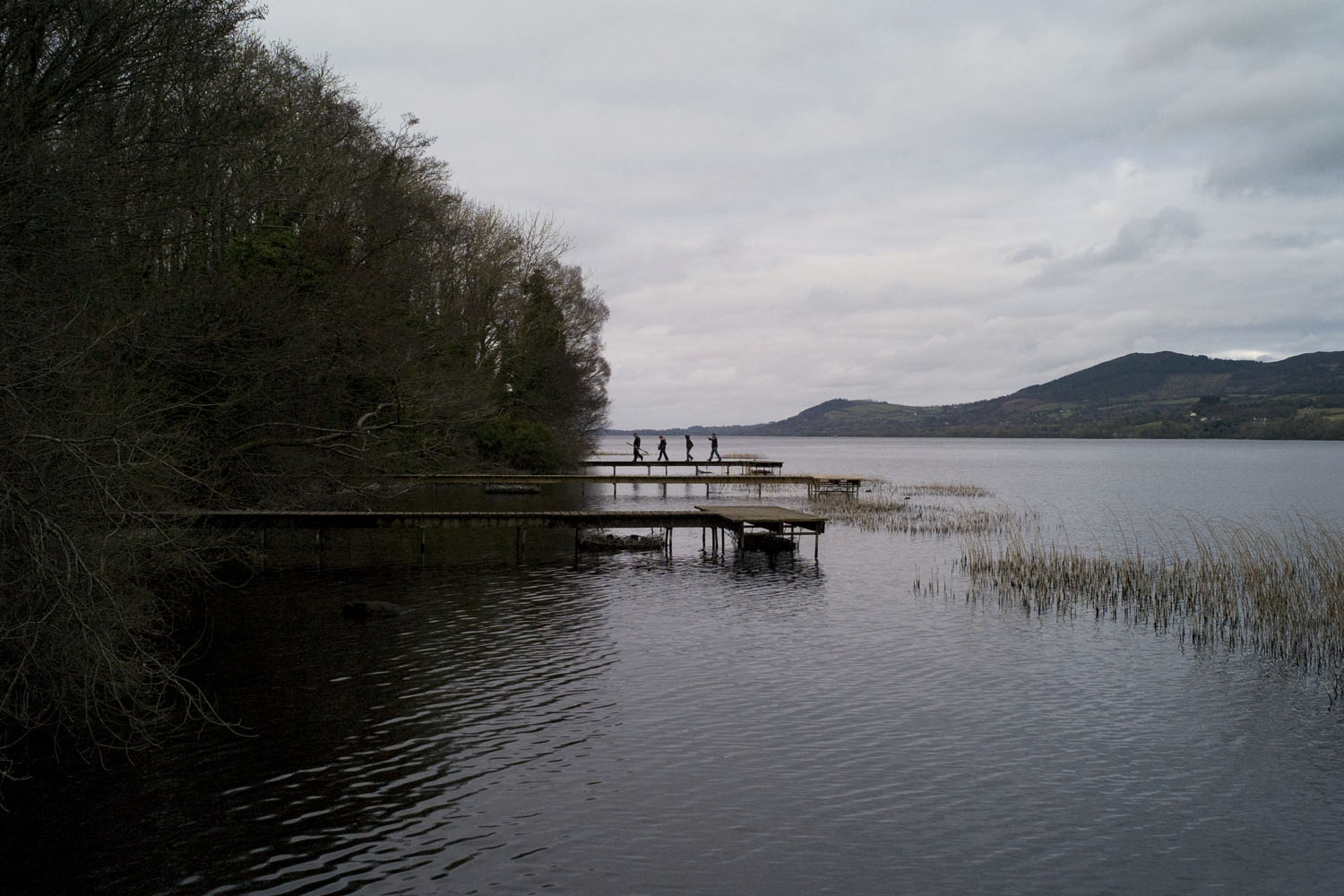 A documentary photograph of people walking on the dock of a lake in the west of ireland