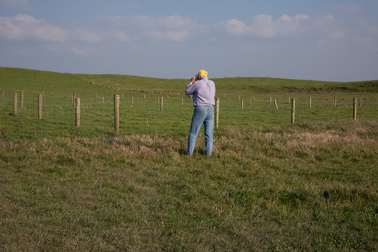 A documentary photograph of a tourist taking photograph of a field in the west of ireland